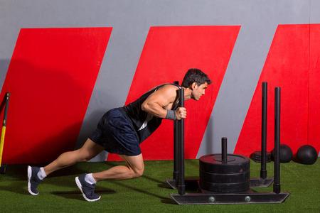 sledge: hombre de empuje trineo empujando el ejercicio de entrenamiento en el gimnasio de pesas Foto de archivo