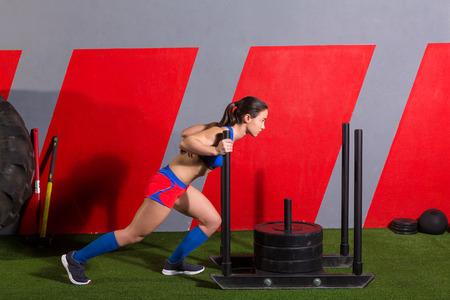 trineo: Mujer empuje trineo empujando pesos ejercicio ejercicios en el gimnasio