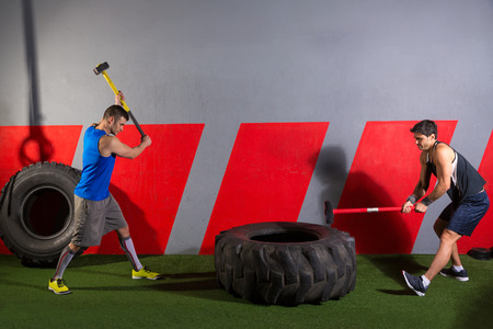 Sledgehammer Tire Hits men workout at gym with hammer and tractor tire photo