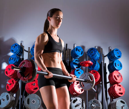 Barbell woman workout fitness club at weightlifting gym photo