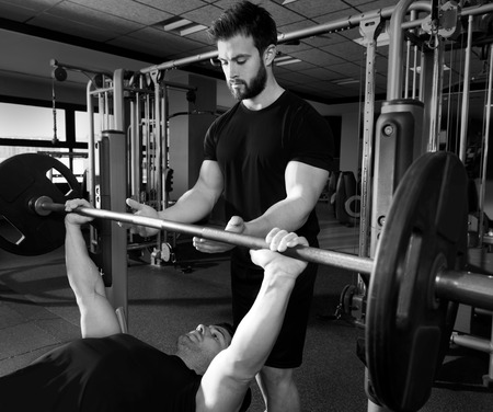 personal trainer: Bench press weightlifting man with personal trainer in fitness gym