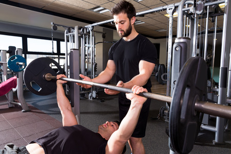 Bench press weightlifting man with personal trainer in fitness gym photo
