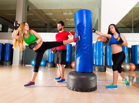 boxing equipment: Boxing aerobox women group with personal trainer man at fitness gym