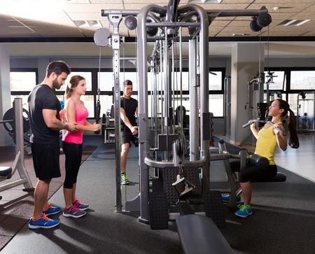 levantando pesas: gimnasia sistema de poleas de cable de entrenamiento gente gimnasio con entrenador personal Foto de archivo