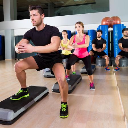 피트니스 체육관 훈련 운동에서 심장 단계 댄스 쪼그리고 앉아서 사람들의 그룹
