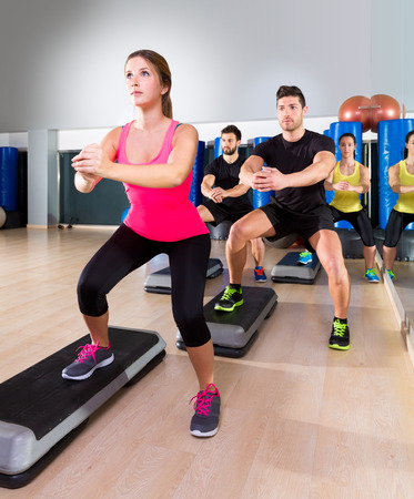 dance steps: Cardio step dance squat people group at fitness gym training workout Stock Photo
