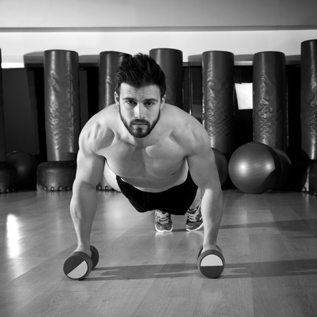 Dumbbells push-ups pushups beard man at fitness gym workout photo