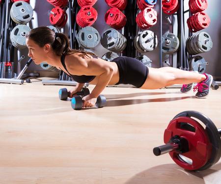 Push-ups femme avec des haltères d'entraînement club de remise en forme au gymnase haltérophilie