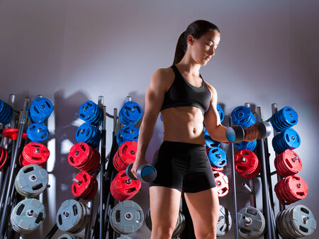 Dumbbell woman workout fitness club at weightlifting gym photo