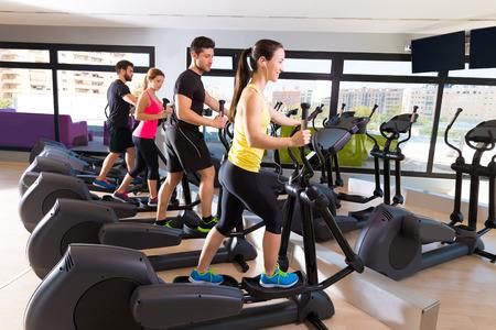 man gym: Aerobics elliptical walker trainer group at fitness gym workout
