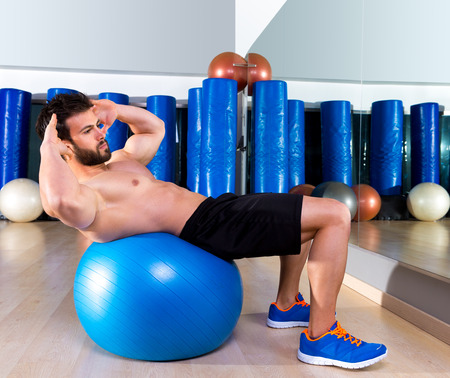 Fitball abdominal crunch Swiss ball man at fitness gym