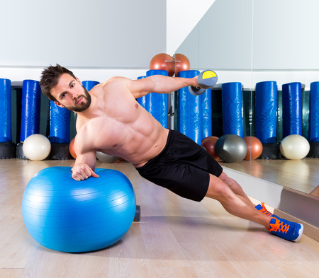 Fitball abdominal side push ups Swiss ball man pushup at fitness gym Stock Photo