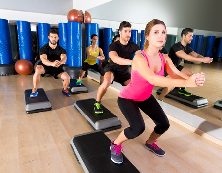 cardio fitness: Cardio step dance squat people group at fitness gym training workout Stock Photo