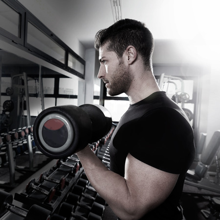 Dumbbell man at gym workout biceps fitness weightlifting Stock Photo