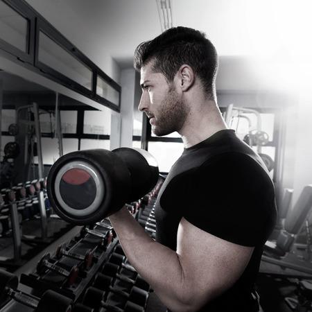 Homme haltère au gymnase biceps d'entraînement de remise en forme haltérophilie