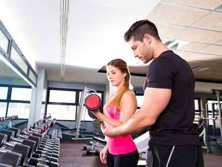 weightlifting equipment: Gym personal trainer man with dumbbell woman fitness weightlifting