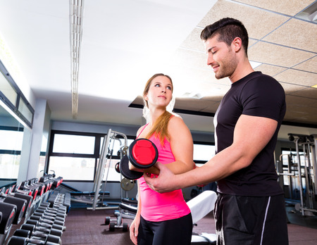 Gym personal trainer man with dumbbell woman fitness weightlifting photo