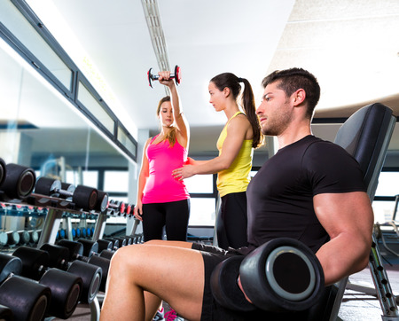woman muscle: Dumbbell man at gym workout fitness weightlifting and dumbbell women personal trainer Stock Photo