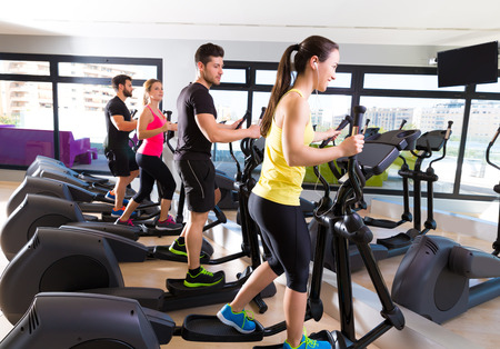 cardio workout: Aerobics elliptical walker trainer group at fitness gym workout