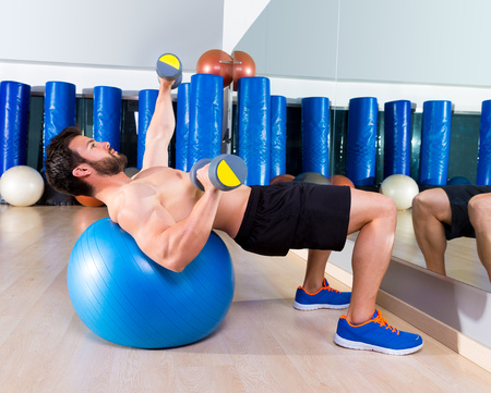 fit ball: Dumbbell chest press on fit ball man workout at fitness gym