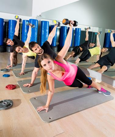 abdomen fitness: Dumbbell empuje hacia arriba de grupo de circuitos de entrenamiento funcional en el gimnasio de fitness Foto de archivo