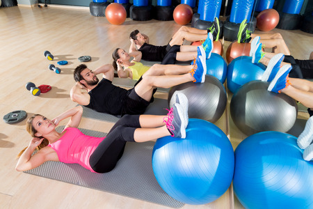 training group: Fitball crunch training group core fitness at gym abdominal workout Stock Photo