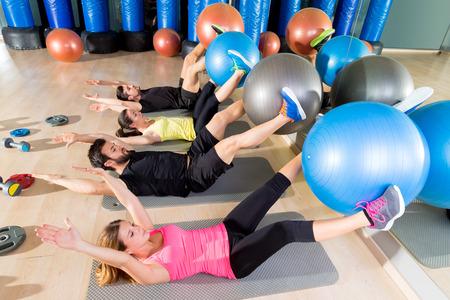Grupo de entrenamiento de fitness crunch Fitball central en la sesión de ejercicios abdominales gimnasio Foto de archivo