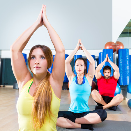Yoga training exercise in fitness gym people group relaxed hands up photo