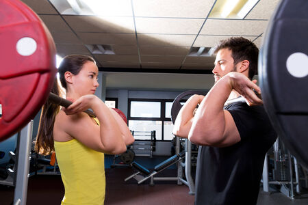 Barbell man and woman workout at fitness gym club photo