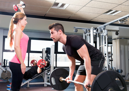 Couple at gym weightlifting workout barbell and dumbbell fitness