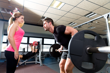 levantar pesas: Pareja en el gimnasio de levantamiento de pesas con barra de ejercicios y fitness mancuernas Foto de archivo