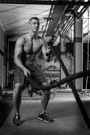 battling: battling ropes man at gym workout exercise fitted body