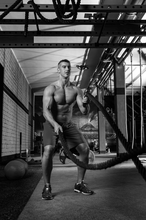 battling ropes man at gym workout exercise fitted body photo