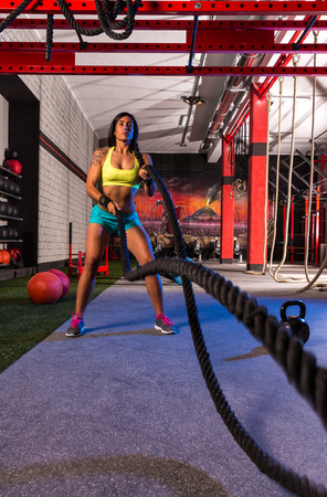 gym girl: battling ropes girl at gym workout exercise fitted body