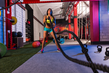 woman rope: battling ropes girl at gym workout exercise fitted body
