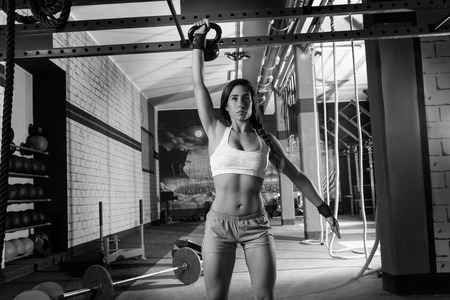 brunette girl at gym lifting a kettlebell weightlifting workout Stock Photo