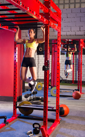 pullups: Toes to bar woman pull-ups 2 bars workout gym Stock Photo