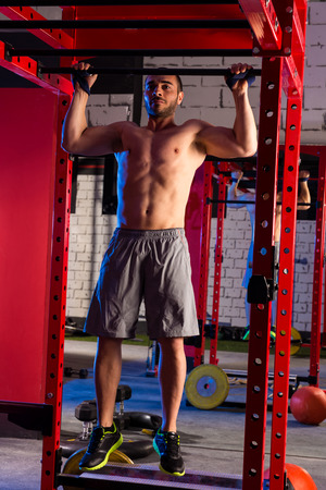 pullups: Toes to bar man pull-ups 2 bars workout gym Stock Photo