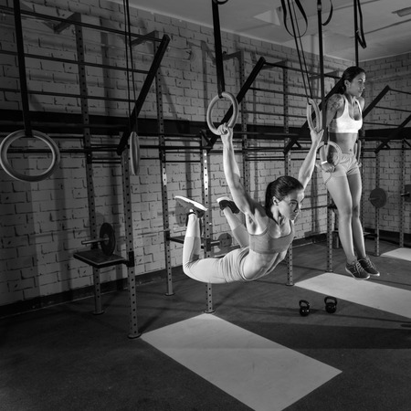 athlete woman: Gym girls muscle ups rings swinging workout at gym Stock Photo