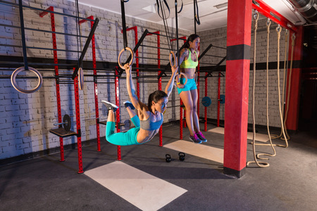hang body: Gym girls muscle ups rings swinging workout at gym Stock Photo