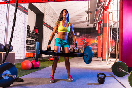 muscle girl: Hex Dead Lift Shrug Bar Deadlifts woman at gym workout weightlifting Stock Photo