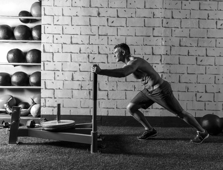 muscle building: sled push man pushing weights workout exercise