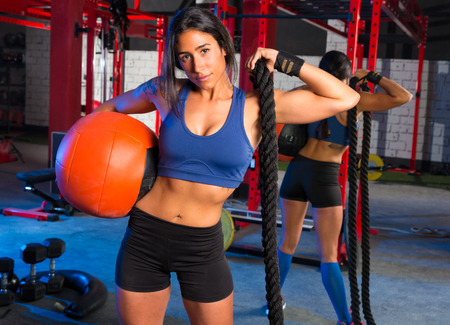weighted: Brunette gym woman with weighted ball and rope posing