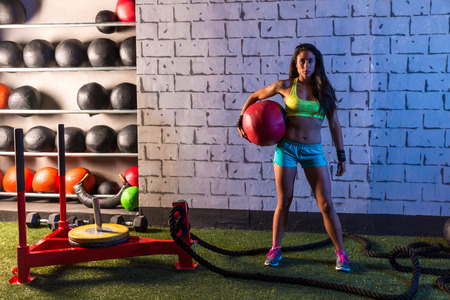 weighted: Brunette gym girl holding weighted ball relaxed Stock Photo