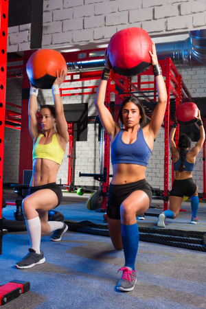 weighted: Gym women weighted ball rising workout exercise together