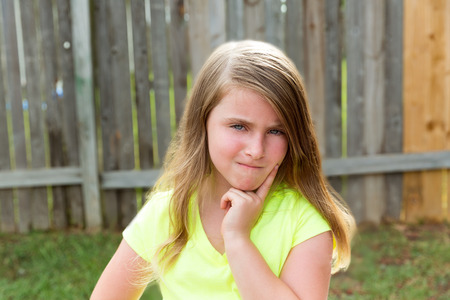 disappoint: kid girl with disappoint expression finger thinking expression outdoor Stock Photo