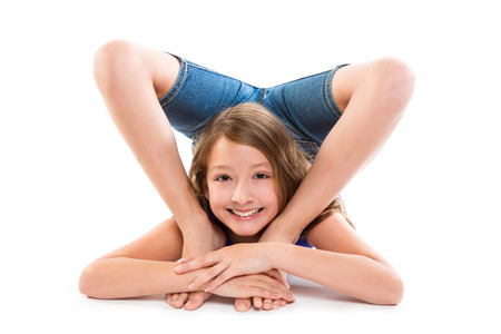 flexibility: Flexible contortionist kid girl playing happy on white background Stock Photo