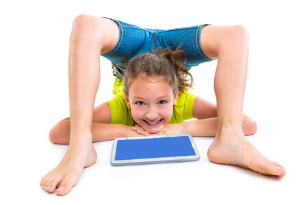 Flexible contortionist kid girl playing with tablet pc on white background photo