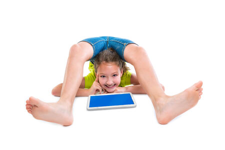 Flexible contortionist kid girl thinking gesture with tablet pc on white background photo