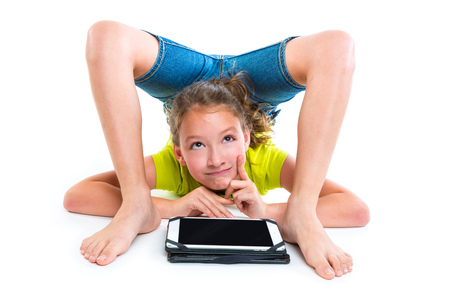 Flexible contortionist kid girl thinking gesture with tablet pc on white background Standard-Bild